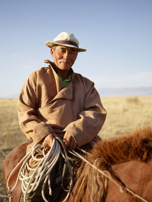 Experienced Mongolian male rider in prairie