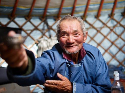 Hospitable senior Asian man in yurt