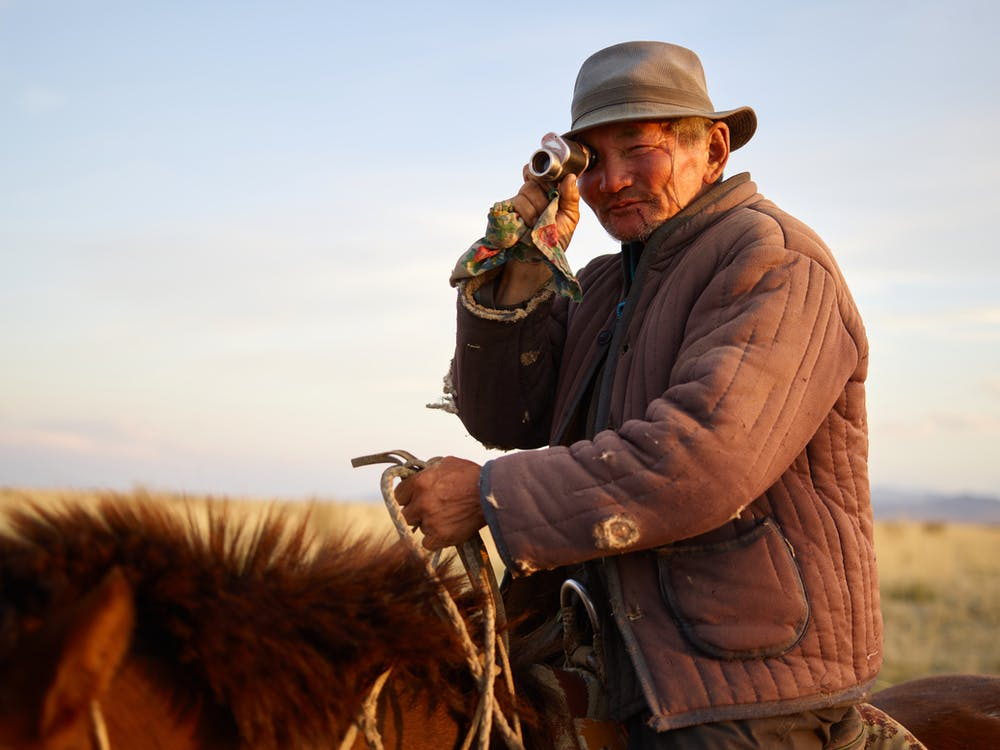 Side view of senior Asian male rider wearing padded jacket with holes looking at camera over shoulder through vintage monocular while riding brown horse on blurred background of yellow steppe and blue sky