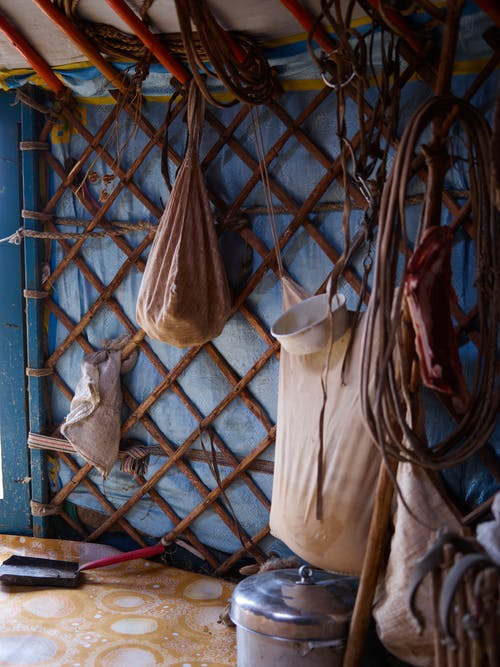 View of inner part of ethnic yurt of Mongolian nomads with domestic utensils and cloth bags for storage near wooden frame of house under tent