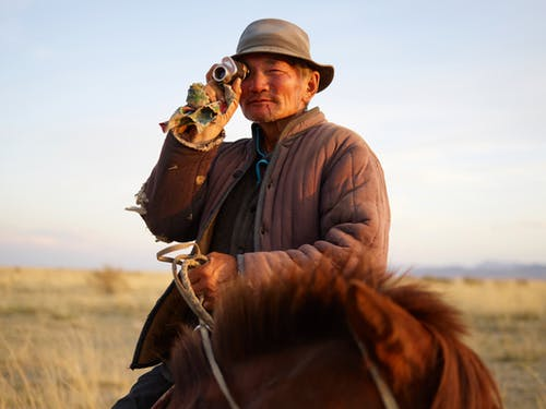 Elderly Asian male farmer wearing old padded jacket looking at camera through vintage monocular while riding brown horse on blurred background of yellow steppe and distant mountains in haze under blue sky
