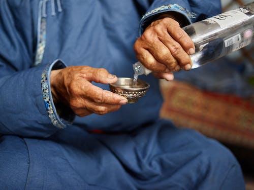 Crop old man pouring vodka in resonance bowl