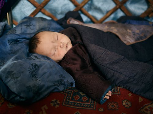 Asian baby sleeping under blanket on carpet