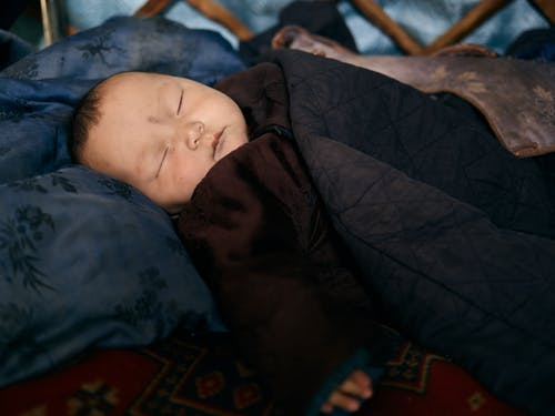 Side view of closeup Asian infant sleeping in warm national clothes under blanket on pillow on carpet