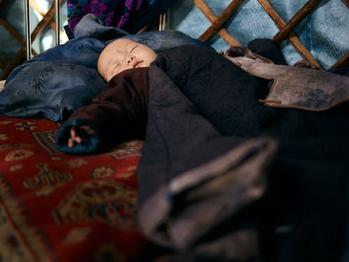 Ethnic baby sleeping in warm clothes on carpet