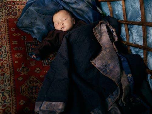 Ethnic baby sleeping under jacket