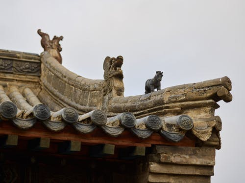 Details of old oriental temple against cloudy sky