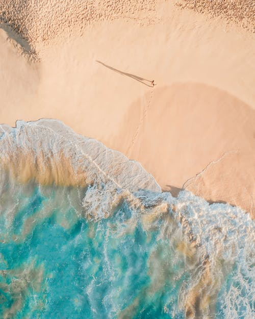 Drone view of anonymous person walking along sandy beach of turquoise sea in sunny day