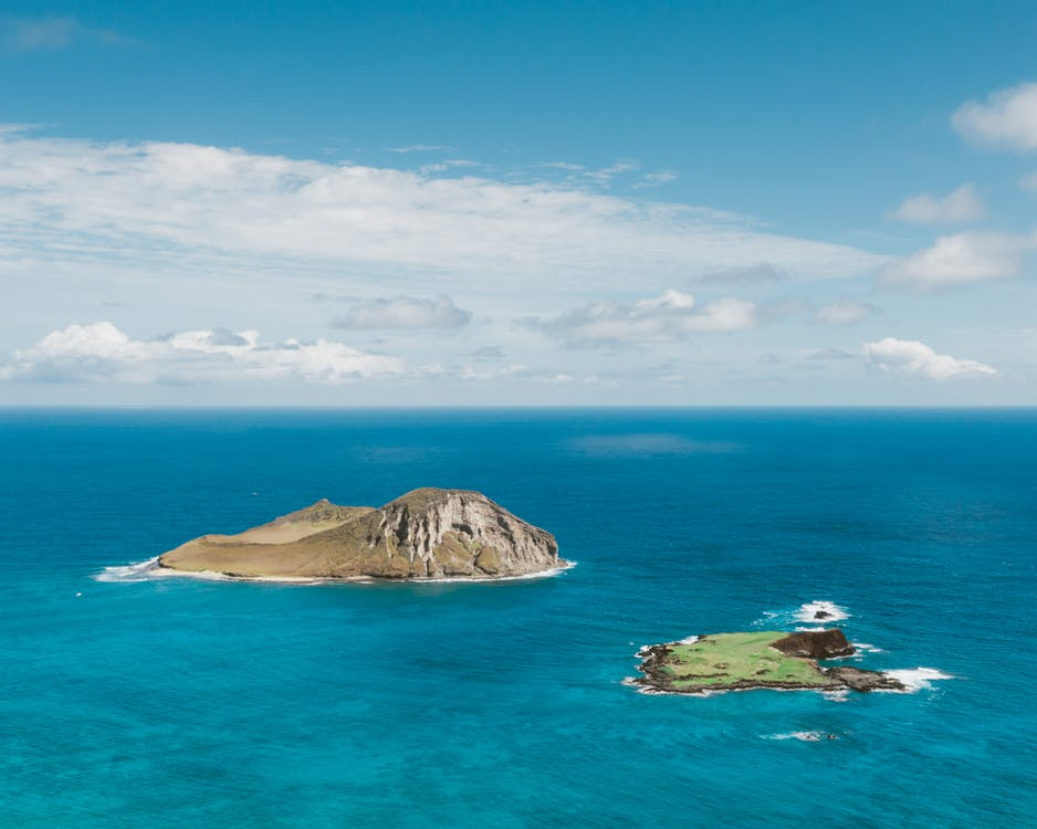 Green and Brown Island on Blue Sea Under Blue and White Cloudy Sky