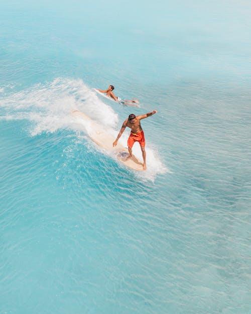 Man in Black Shorts Surfing on Blue Ocean Water