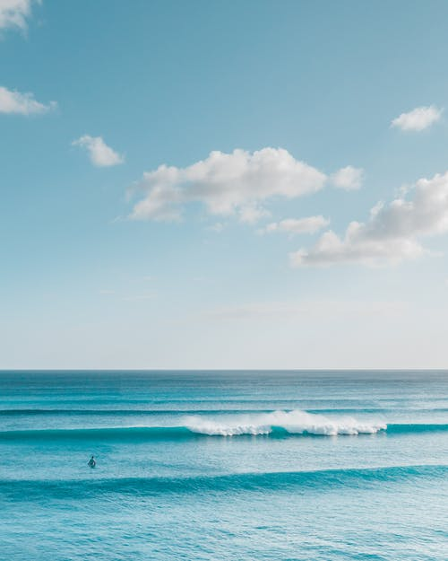 Ocean Waves Under Blue Sky and White Clouds