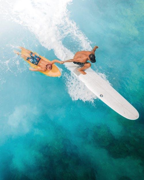 Woman in Orange Bikini Lying on White Surfboard on Water