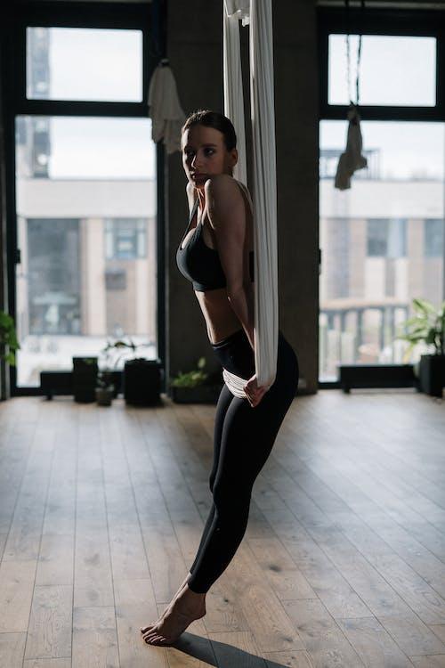 Woman in Black Sports Bra and Black Leggings Standing Near Glass Window