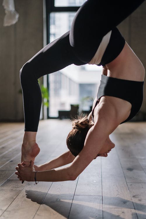 Woman in Black and White Sports Bra and Black Leggings Doing Yoga