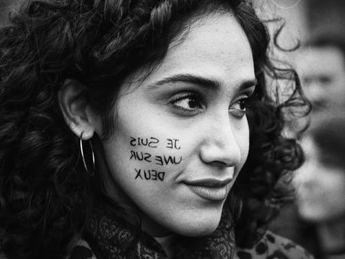 Positive young ethnic woman with text on face