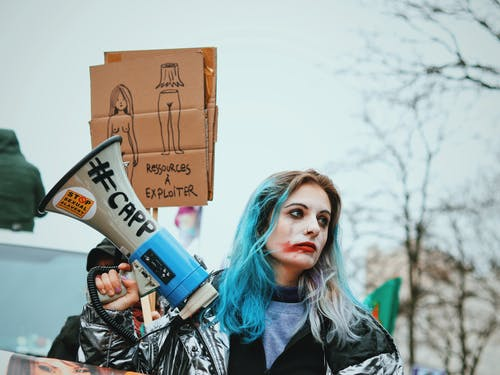 Eccentric young female with blue hair and painted face standing on street with loudspeaker and banner during protest action