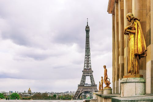Low angle of golden statues of historical Palais de Chaillot and Eiffel Tower against cloudy sky in Paris