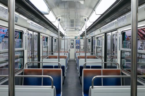 Empty illuminated subway train with seats and metal railings stopped on platform at station
