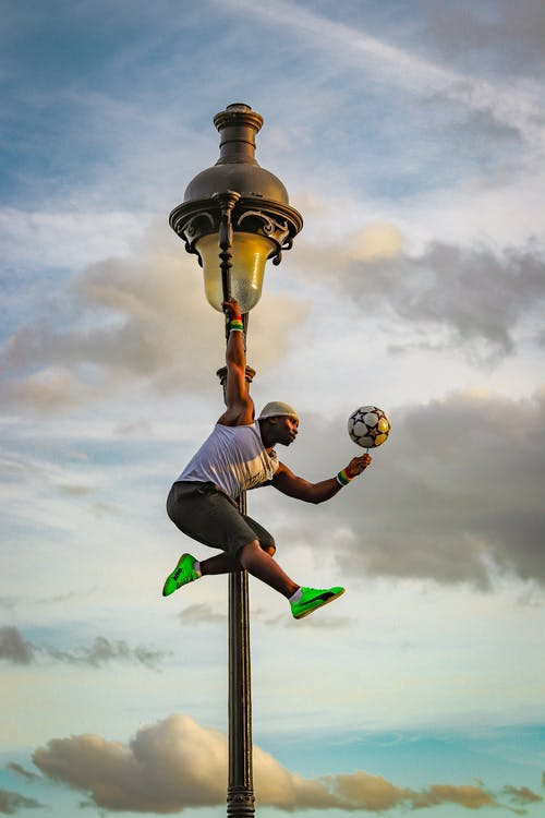 Strong black sportsman jumping on street near lantern and rolling ball on finger
