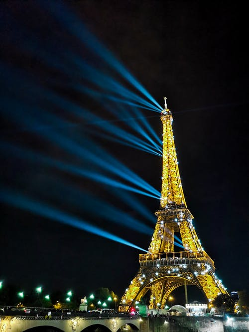 From below of bridge and famous sparkling Eiffel Tower with luminous lamps and spotlights against dark night sky in Paris