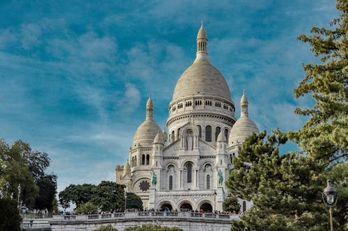 Low angle exterior of famous Sacre Coeur Basilica with domes and arched windows located on Montmartre hill in Paris against blue sky
