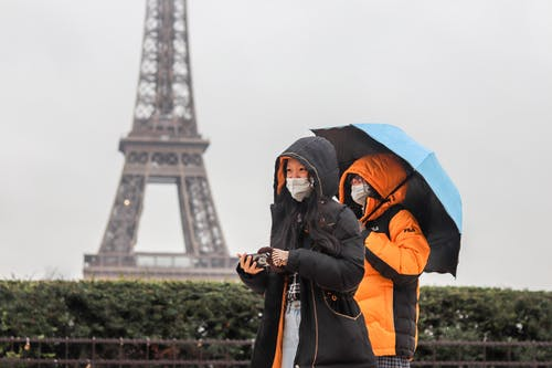 Anonymous ethnic tourists walking along street on foggy rainy day in Paris