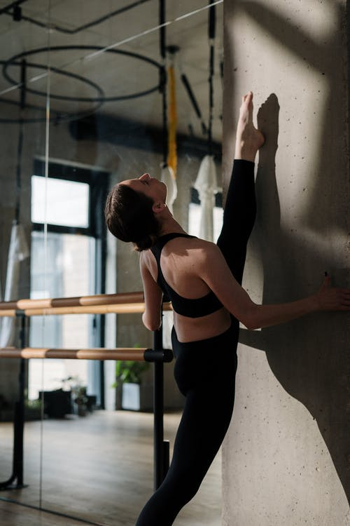Woman in Black Tank Top and Black Leggings Leaning on White Wall