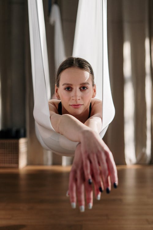 Girl in White Long Sleeve Shirt Lying on Brown Wooden Floor