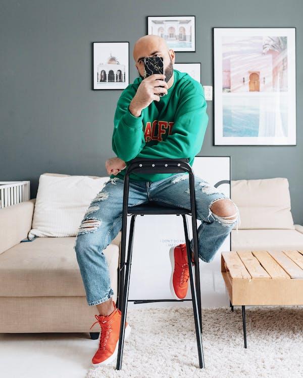 Causal bored man taking selfie in modern room