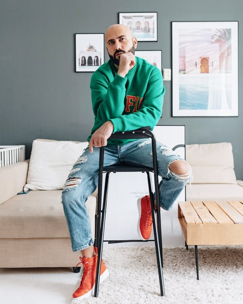 Full length bald male in trendy hoodie and denim leaning on hand while sitting on stool in apartment looking away