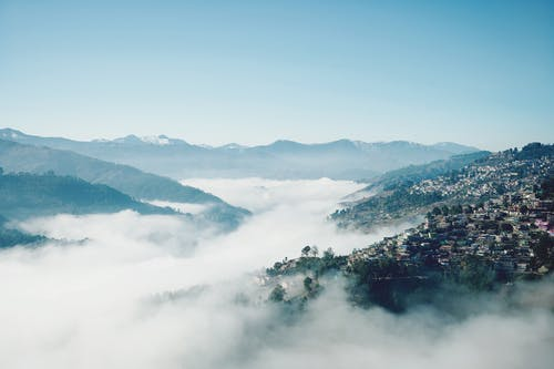Aerial View of Mountains and Trees Covered by Clouds