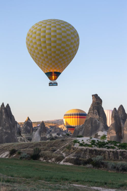 Flying green hot air balloon above ground with peaky rocks during festival in nature