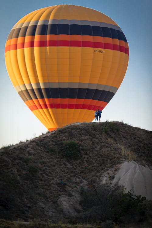 Colorful hot air balloon above hill