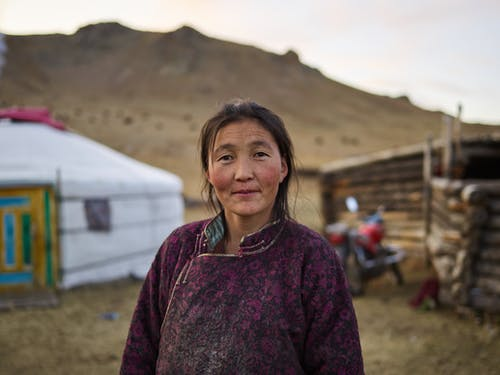 Adult ethnic woman in national dress looking at camera while standing against traditional ger in valley