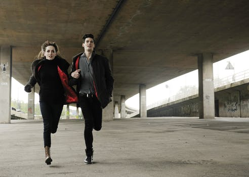 Man and Woman Running Under Bridge