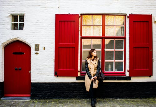 Elegant woman at old building with red shutters