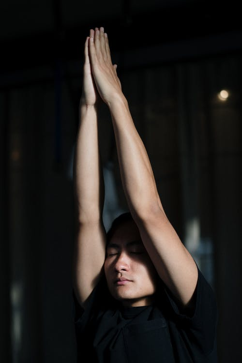 Man in Black T-shirt Raising His Hands