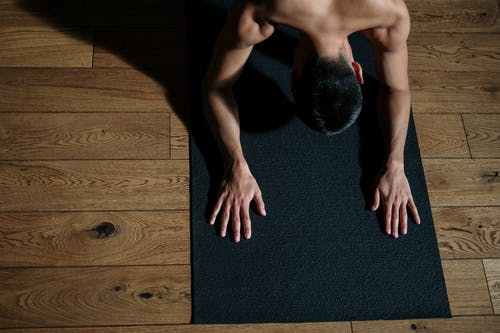 Topless Man Sitting on Black Area Rug