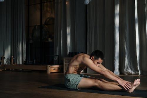 Topless Man in Blue Denim Jeans Sitting on Brown Wooden Floor