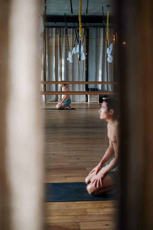 Topless Man Sitting on Brown Wooden Floor