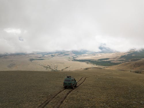 Aerial view of old green SUV car driving along empty endless valley under thick clouds