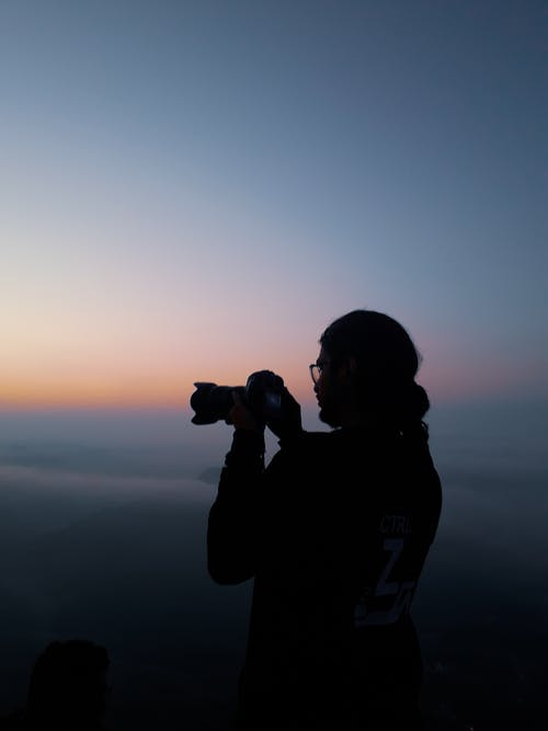 Anonymous photographer taking pictures of sunset