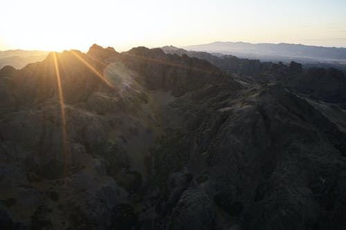 Majestic drone view of mountain range almost plunged into darkness touched by last sunbeam of setting sun causing lens flare