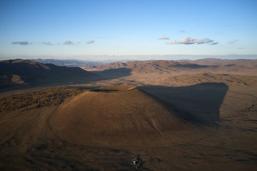 Drone view of round volcano mount casting dark shadow on big valley surrounded with mountain ranges under clear blue sky at sunset