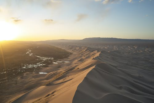 Sand hills in desert at sunset