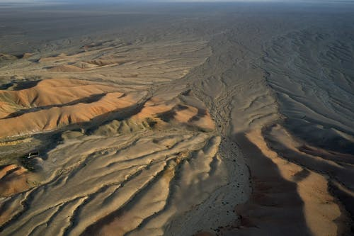 Top view of desolated sand ribbed surface with barren soil and small puddles in desert in daylight