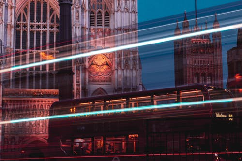 Long exposure of trails of light and double decker bus against medieval buildings at night in city