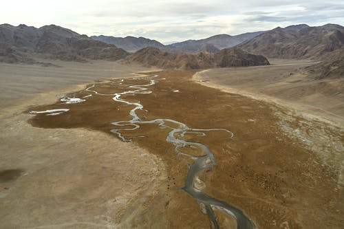 Drone view of narrow riverbeds flowing on rough terrain near mountains in daytime