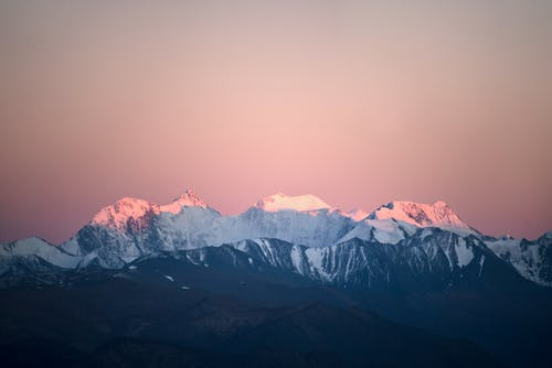 Wonderful view mountains ridge covered with white snow enlightened with bright pink sunrise sun under purple sky