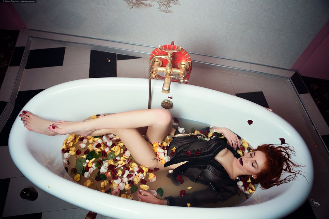 Woman Lying in Bathtub With Flowers